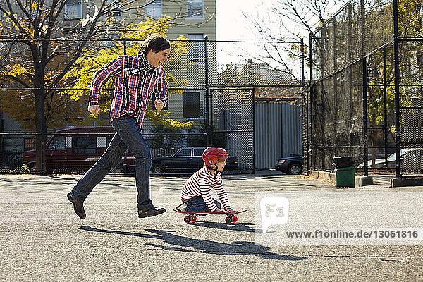 Seitenansicht eines Mannes  der rennt  während sein Sohn im Park Skateboard fährt