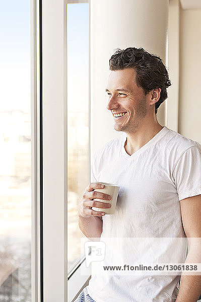 Smiling man drinking coffee and looking though window