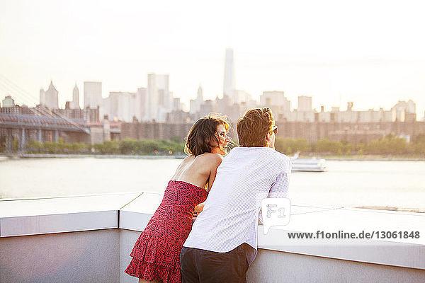 Rückansicht eines Paares  das sich bei Sonnenuntergang an ein Geländer lehnt