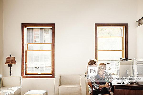 Familie betrachtet Desktop-Computer zu Hause