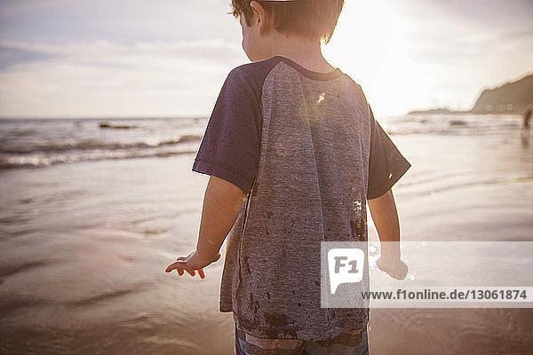 Jungen am Strand bei Sonnenuntergang mittig geschnitten