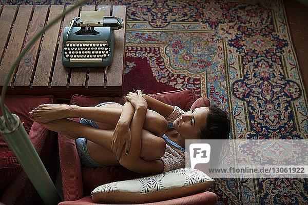 Hochwinkelansicht einer nachdenklichen Frau auf Sesseln zu Hause