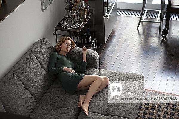 Hochwinkelansicht einer Frau  die zu Hause auf dem Sofa liegt