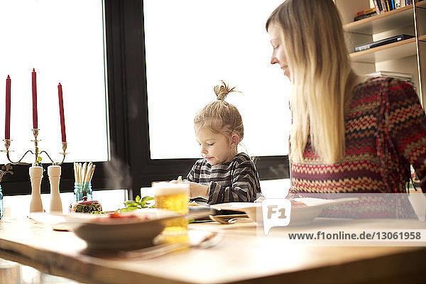 Mother looking at girl having food at table