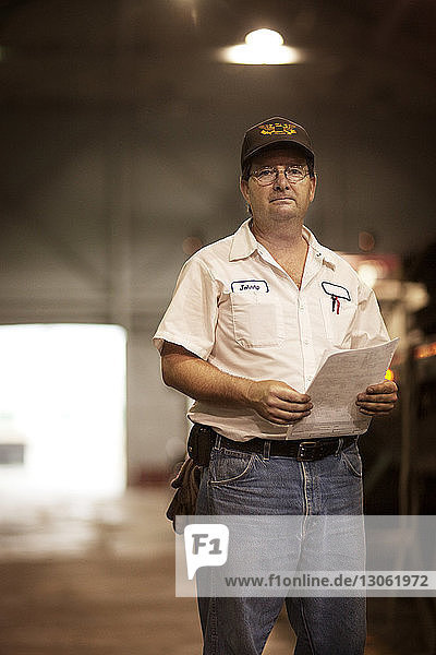 Portrait of man holding document while standing in industry