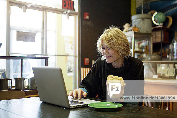 Happy woman using laptop while sitting at table in cafe