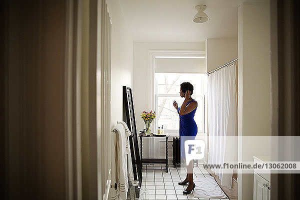 Side view of woman standing by mirror and getting dressed at home