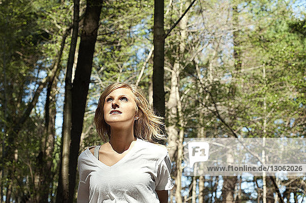 Thoughtful woman looking away in forest