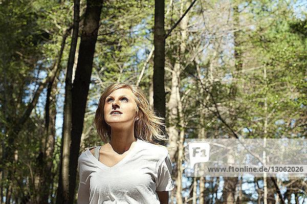 Nachdenkliche Frau schaut im Wald weg