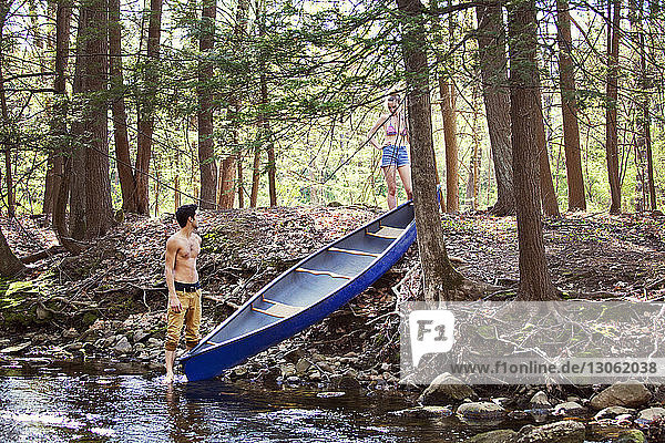 Couple with rowboat standing in forest