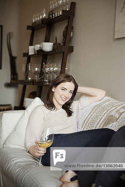 Portrait of smiling woman holding wineglass while resting on sofa at home