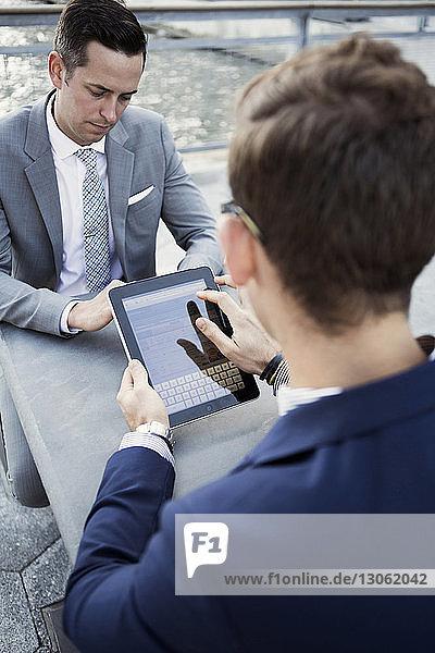 Geschäftsmann benutzt digitales Tablett  während er mit seinem Kollegen am Tisch sitzt