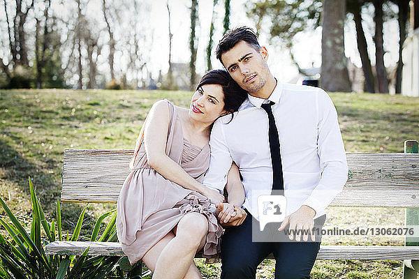 Porträt eines glücklichen Paares auf einer Parkbank sitzend