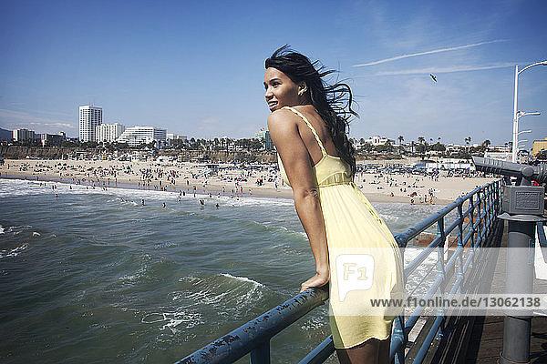 Frau  die am Geländer steht und den Blick gegen den Himmel richtet