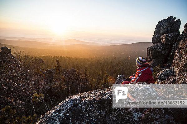Frau sitzt auf Felsen am Berg gegen den Himmel bei Sonnenuntergang