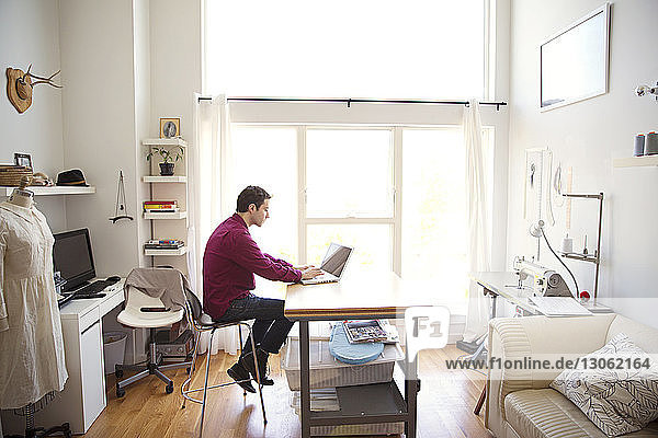 Male fashion designer working on laptop at table in creative office
