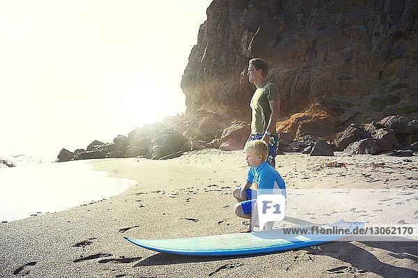 Vater und Sohn mit Surfbrett am Strand an der Steilküste