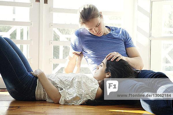 Frau entspannt sich zu Hause auf dem Schoß des Mannes