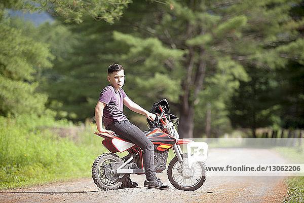 Portrait of boy sitting on dirt bike