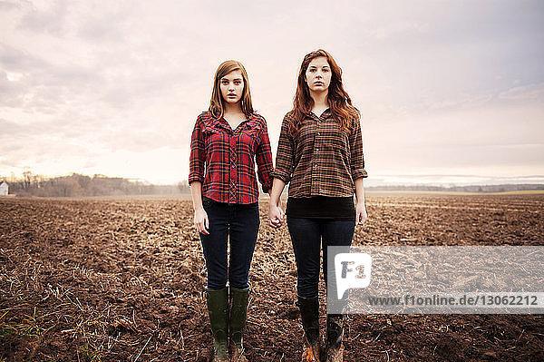 Porträt von Freundinnen  die sich an den Händen halten  während sie auf dem Feld stehen