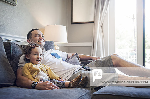 Happy father and daughter relaxing on sofa at home
