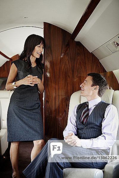 Happy businessman looking at female colleague while traveling in corporate jet