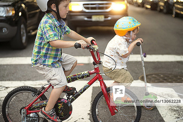Brothers riding push scooter and bicycle on road