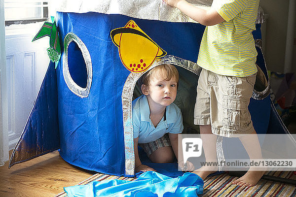 Siblings playing in tent at home