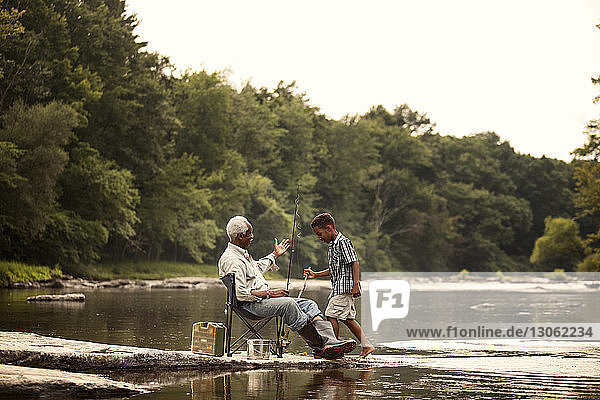 Man with grandson at lake against clear sky