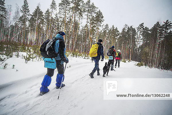 Rear view of friends carrying backpack while walking on snow covered field