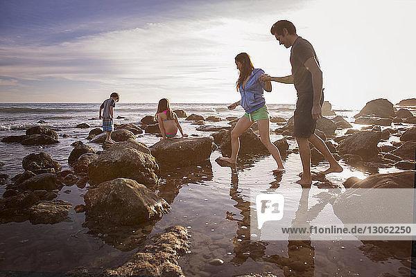 Paar hält sich an den Händen  während Kinder am Strand am Felsen spielen
