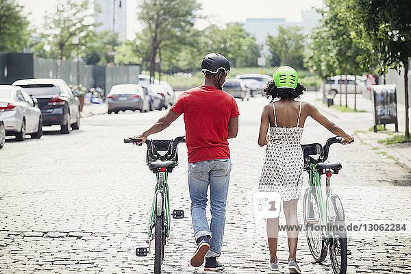 Rückansicht eines Paares mit Fahrrädern  das in der Stadt auf der Straße geht