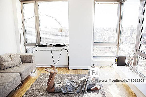 Hochwinkelansicht einer Frau  die ein Mobiltelefon benutzt  während sie zu Hause auf dem Boden liegt
