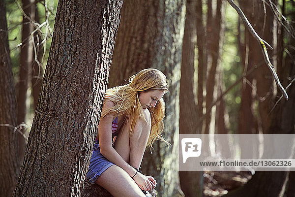Sad woman sitting in forest