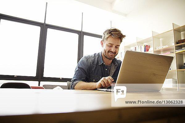 Glücklicher Mann mit Laptop am Tisch