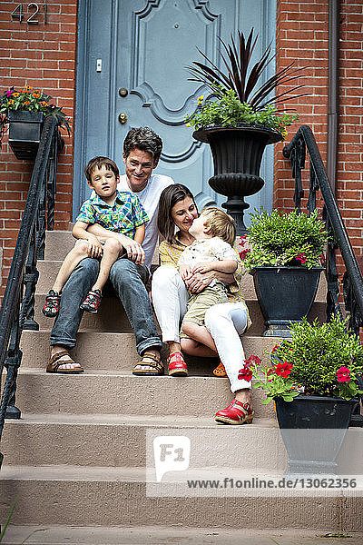 Happy family sitting on steps outside house