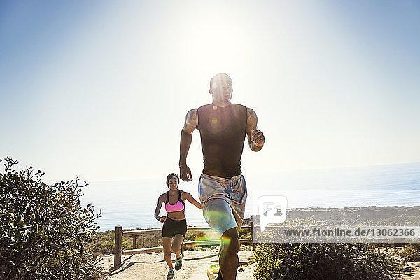 Paar rennt auf Berg gegen klaren Himmel