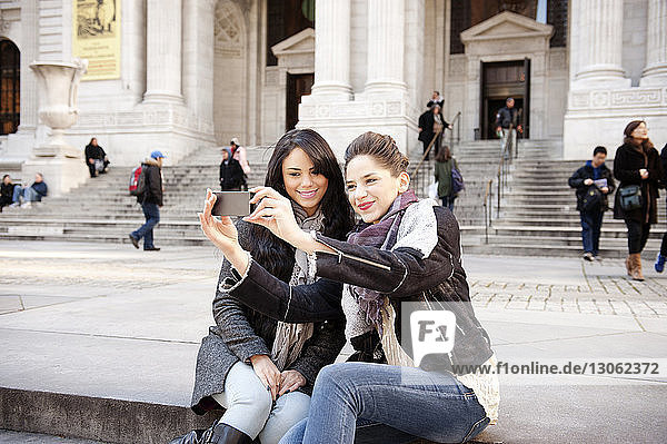 Happy female friends clicking selfie with smart phone while sitting on steps