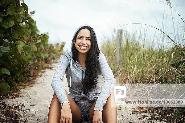 Porträt einer glücklichen Frau am Strand sitzend