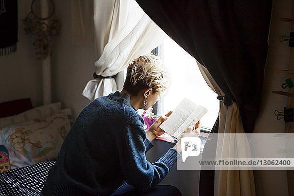 Hochwinkelansicht einer Frau  die ein Buch liest  während sie zu Hause am Fenster sitzt
