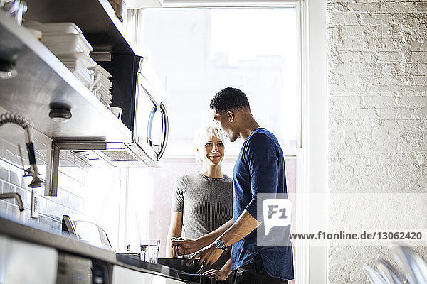 Man looking at woman while preparing food in kitchen