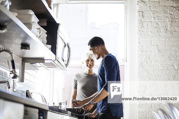 Mann schaut Frau an  während er in der Küche Essen zubereitet