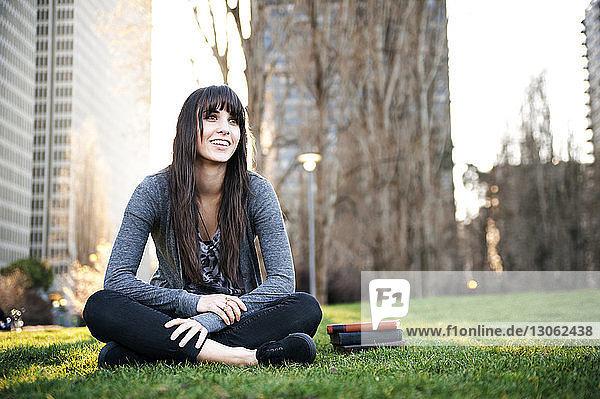 Frau schaut weg  während sie auf einem Grasfeld sitzt