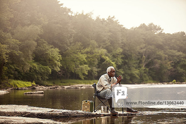 Thoughtful man with fishing rod sitting on chair by lake