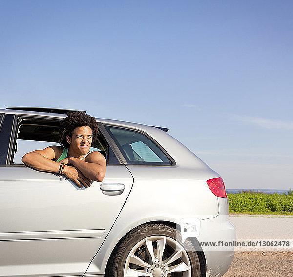 Happy man looking through car window against clear sky