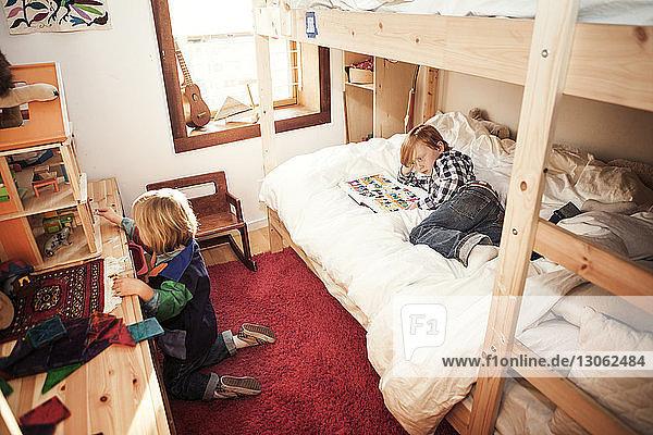 Hochwinkelansicht von Kindern im häuslichen Schlafzimmer