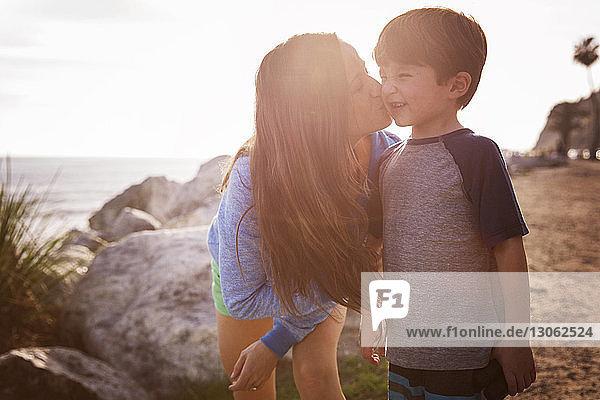 Glückliche Mutter küsst Sohn am Strand bei Sonnenuntergang