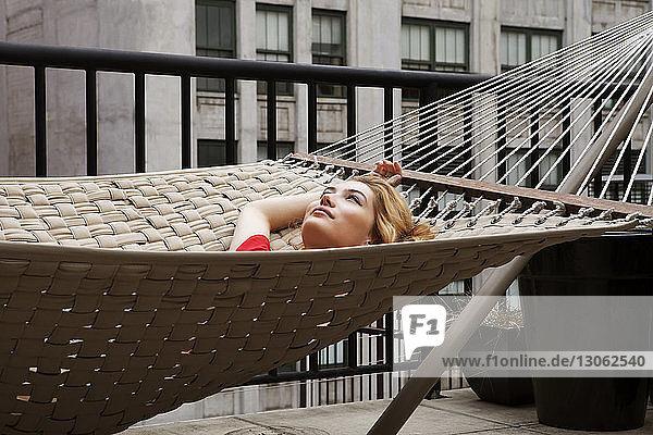 Nachdenkliche Frau liegt auf Hängematte im Innenhof