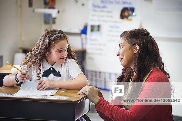Lächelnde Lehrerin schaut Schulmädchen im Klassenzimmer an