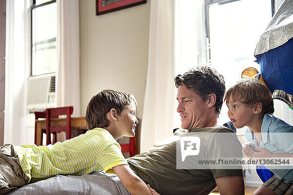 Happy father relaxing with sons at home